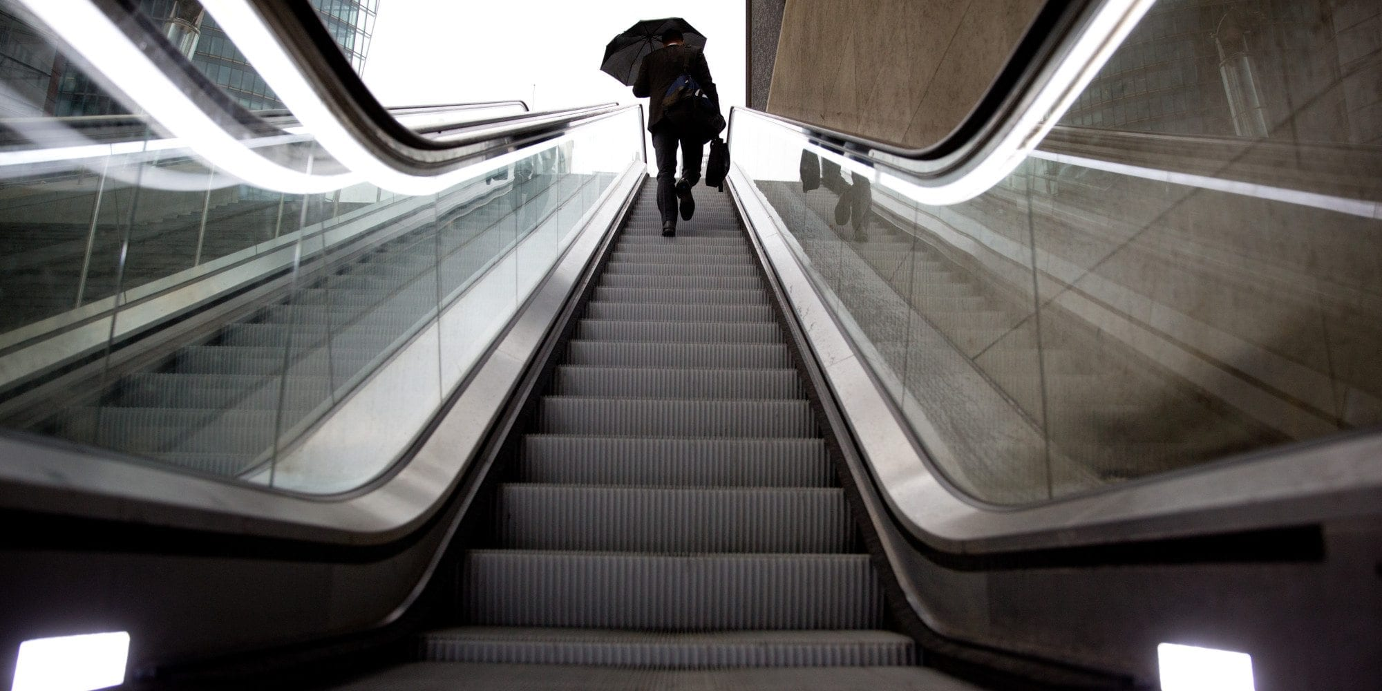 A man uses an umbrella to shelter from the rain as he takes an escalator at Potsdamer Platz square on September 9, 2013 in Berlin. Temperatures in the German capital were around 14 degrees Celsius. AFP PHOTO / DPA / KAY NIETFELD / GERMANY OUT (Photo credit should read KAY NIETFELD/AFP/Getty Images)